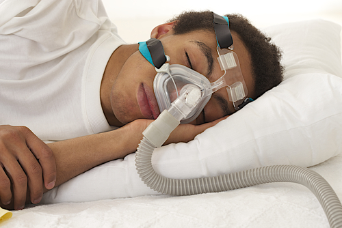 Young man sleeping with his CPAP mask on.
