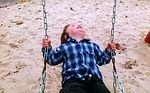 child_playing_on_swing