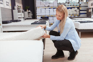 Woman picking out her perfect mattress.