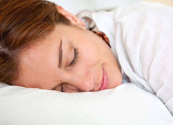 Beautiful woman sleeping over a white pillow.
