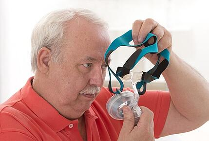 Man trying on CPAP masks.
