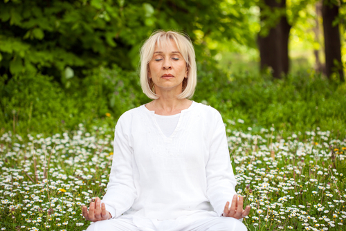 Older woman doing her daily meditation exercises.
