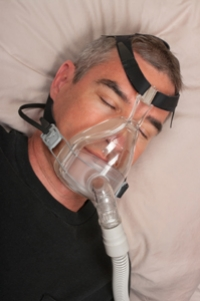 Man using is CPAP machine for OSA.