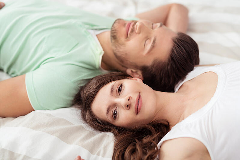 Close up Pretty Woman Smiling at the Camera While Lying on Bed Beside her Handsome Boyfriend in Opposite Direction.
