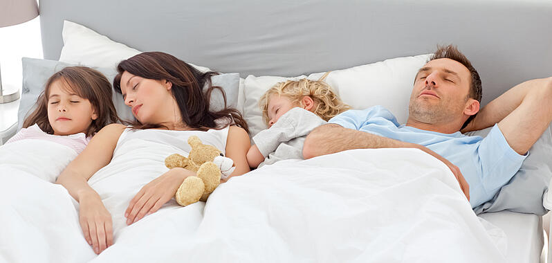 Cute family sleeping together in the parentss bed