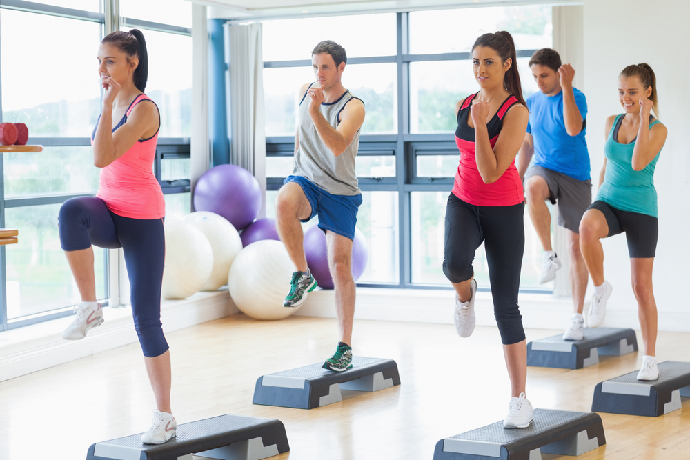 Full length of instructor with fitness class performing step aerobics exercise in gym