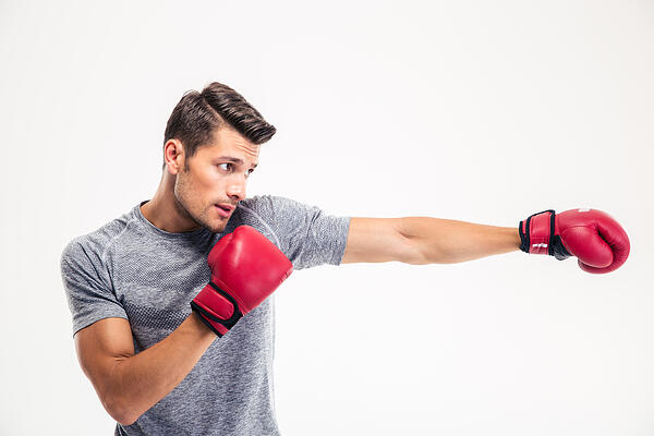 Side view portrait of a handsome man boxing.