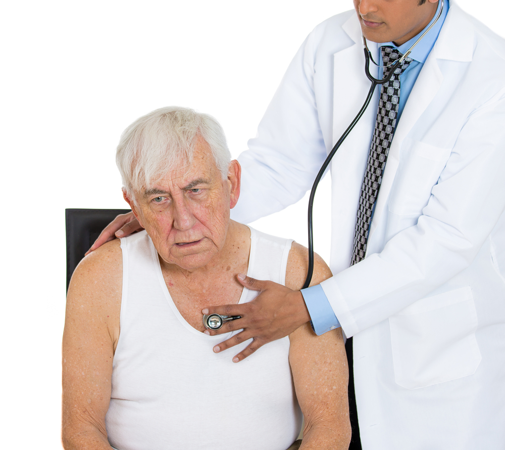 A closeup cropped portrait of a doctor performing heart lungs chest physical exam  listening with stethoscope on an elderly senior mature man sitting on black chair, isolated on a white background.