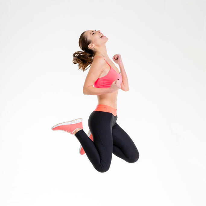 Attractive excited fitness girl in sportwear jumping of joy isolated over white background