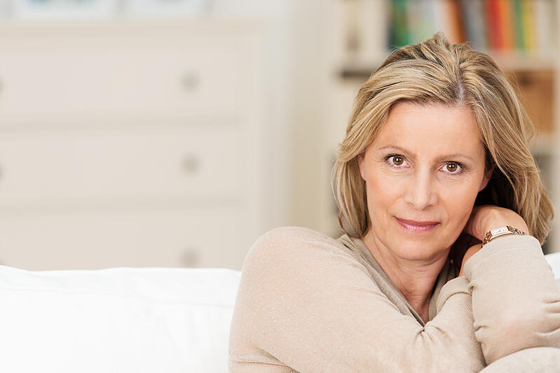 Attractive sincere middle-aged woman sitting on a sofa leaning her head on her raised arm looking directly at the camera with a serious expression