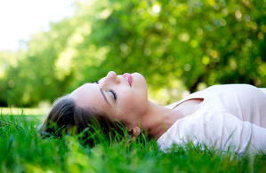 Beautiful woman relaxing outdoors lying on the floor