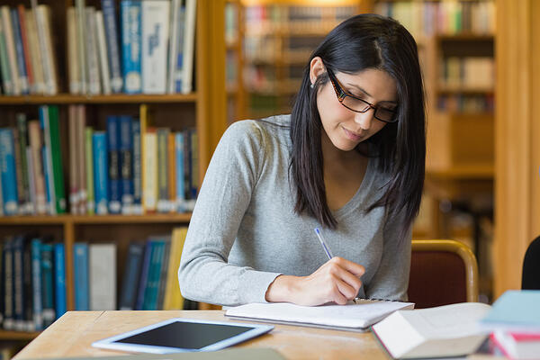 Black-haired woman studying in the library
