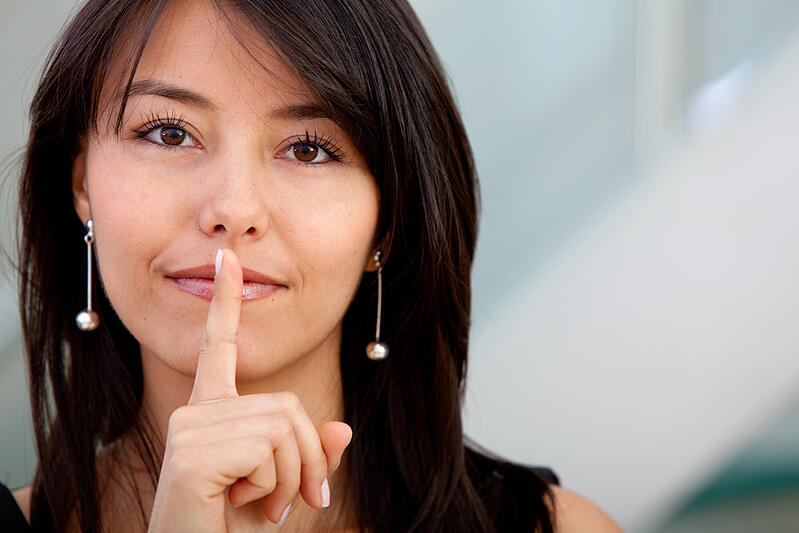 Business woman making a silence sign with her hand