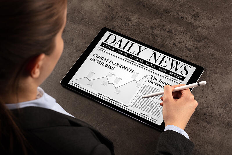 Business woman reading news on tablet