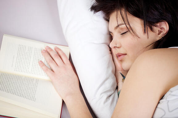 Cheerful woman falling asleep while reading book in a close up shot