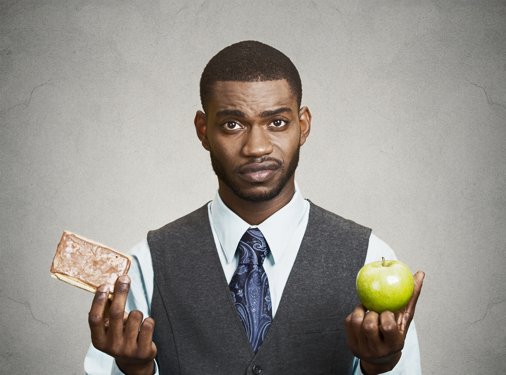 Closeup portrait headshot corporate executive, businessman trying to decide on diet, sweet cookie versus green fresh apple isolated black grey background. Weight control eating habits. Face expression