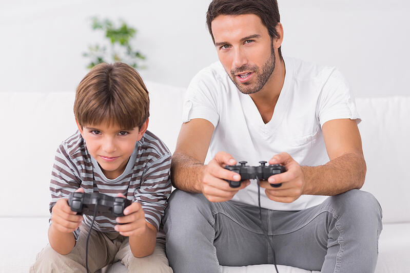 Father and son playing video games on the couch
