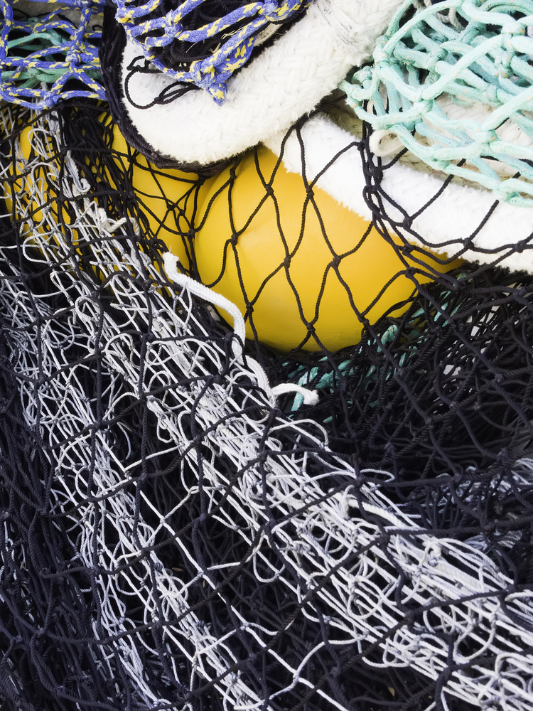 Fishing nets with yellow fender in a marina storage pile outdoors