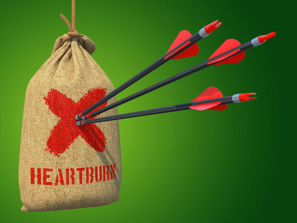 Heartburn - Three Arrows Hit in Red Target Hanging on the Sack on Green Background