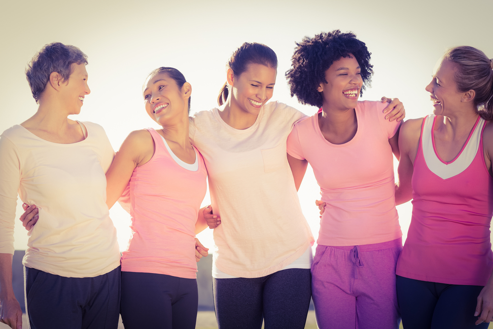 Laughing women wearing pink for breast cancer .