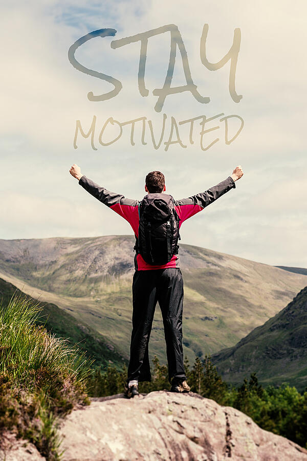 Man standing at hill top cheering against stay motivated