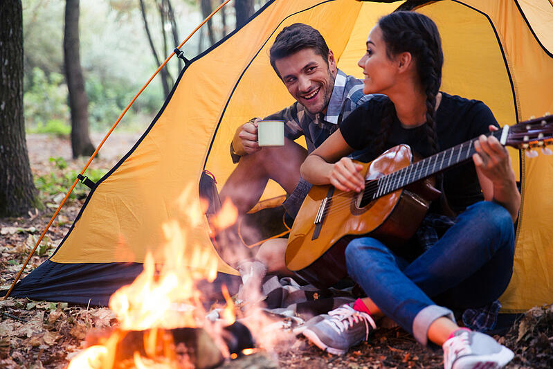 Portrait of a young couple sitting with guitar near bonfire in the forest-1