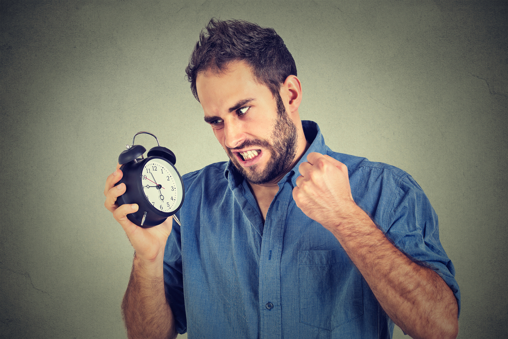 Portrait upset angry young man screaming at alarm clock isolated on gray wall background. Employee running late. Time management concept