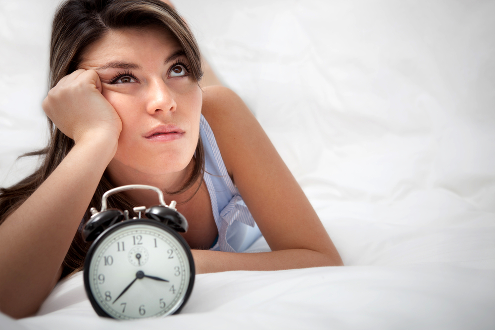 Sleepless woman lying in bed looking at the hours pass by-1