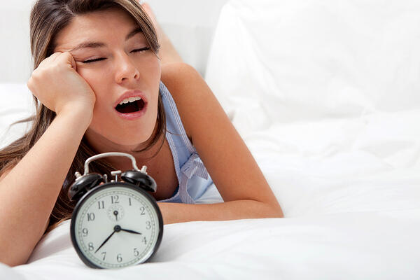 Sleepless woman lying in bed looking at the hours pass by-3