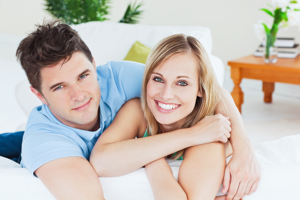 Smiling beautiful couple sitting on a sofa looking at the camera