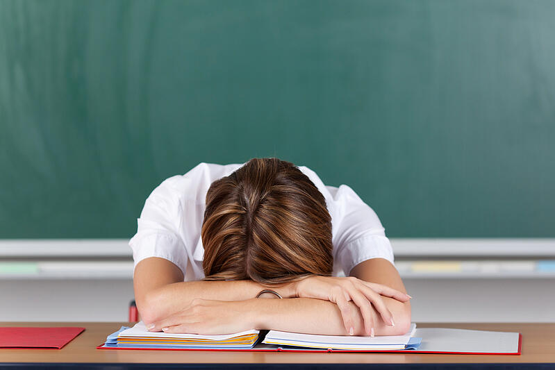 Teacher suffering from acute stress resting her head on her arms at her desk in front of the blackboard as she seeks to gather herself together