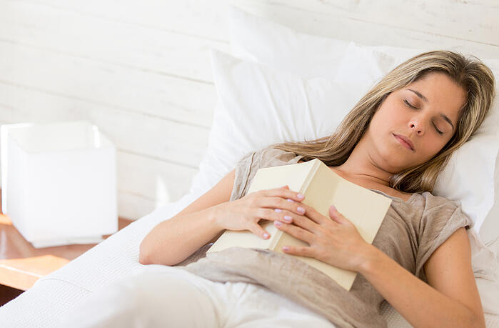 Tired woman reading a book and falling asleep