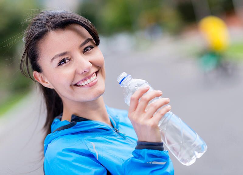 Woman hydrating after workout drinking water from a bottle