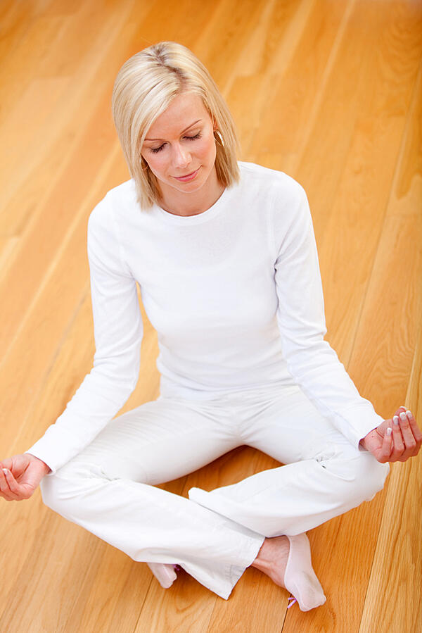 Woman wearing white clothes doing yoga - indoors