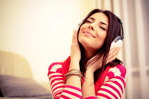 Young beautiful woman in bright outfit enjoying the music at home