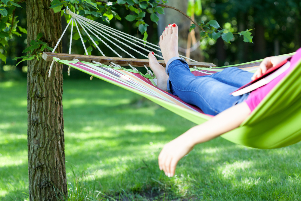 Young lady resting on hammock with book summer-1