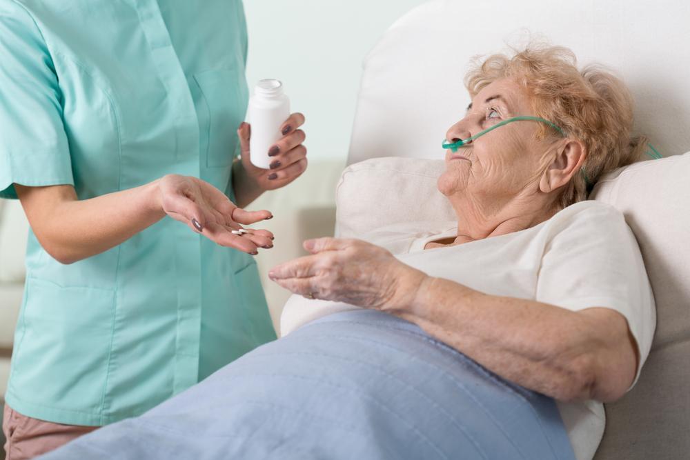 Young nurse giving the pills to her sick older patient