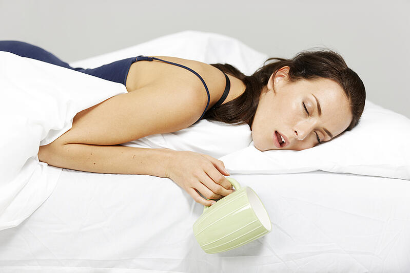 Young woman falling asleep in bed with drink in hand-1