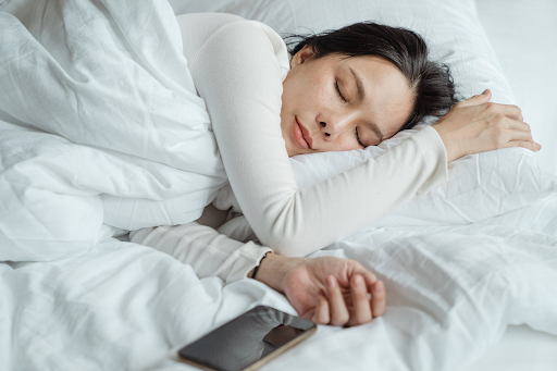 Woman falling asleep with cell phone in bed.