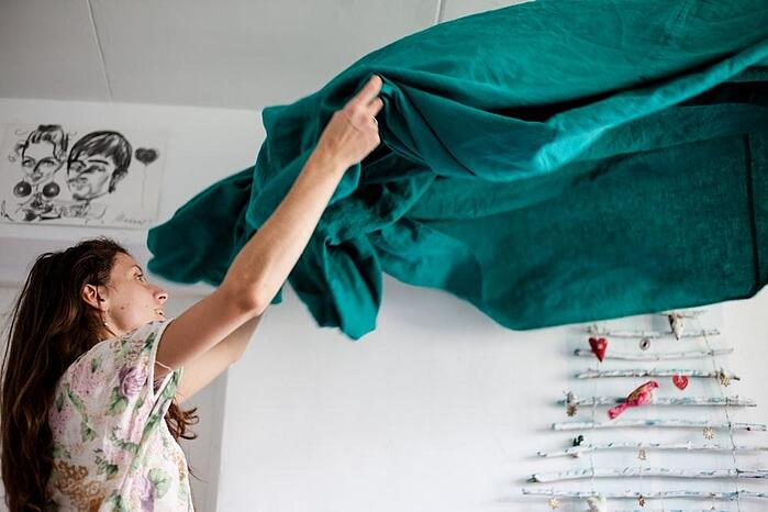 Woman putting clean sheets on her bed.