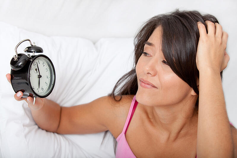 Woman waking up and running late looking at the alarm clock