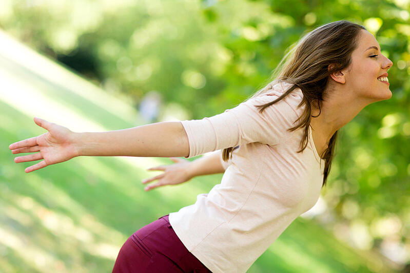 Woman with arms open enjoying nature at the park