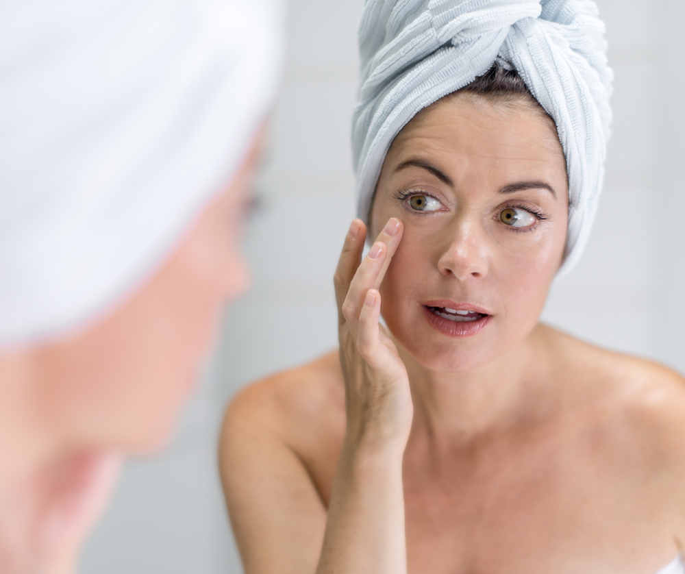 portrait of a beautiful mature lady with a towel on her head looking at her skin in the mirror