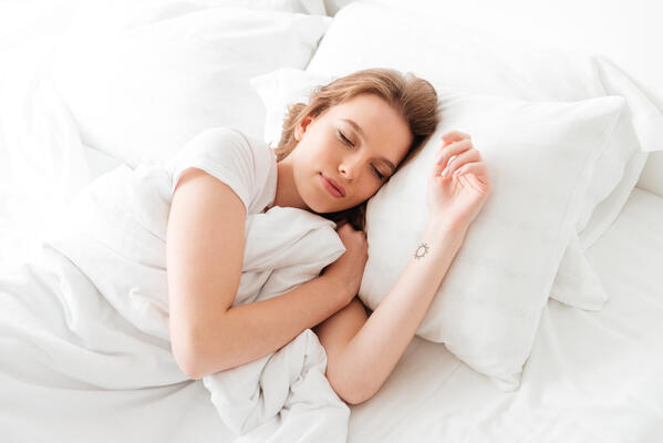 Woman sleeping comfortably in her bed.