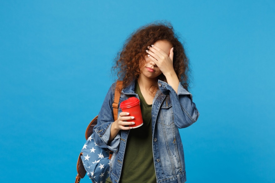 teen-student-denim-clothes-backpack-hold-paper-cup-isolated-blue-wall