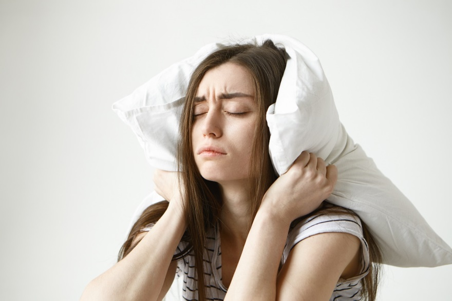 woman-trying-have-some-sleep-sitting-bedroom-with-pillow-her-head-closing-eyes