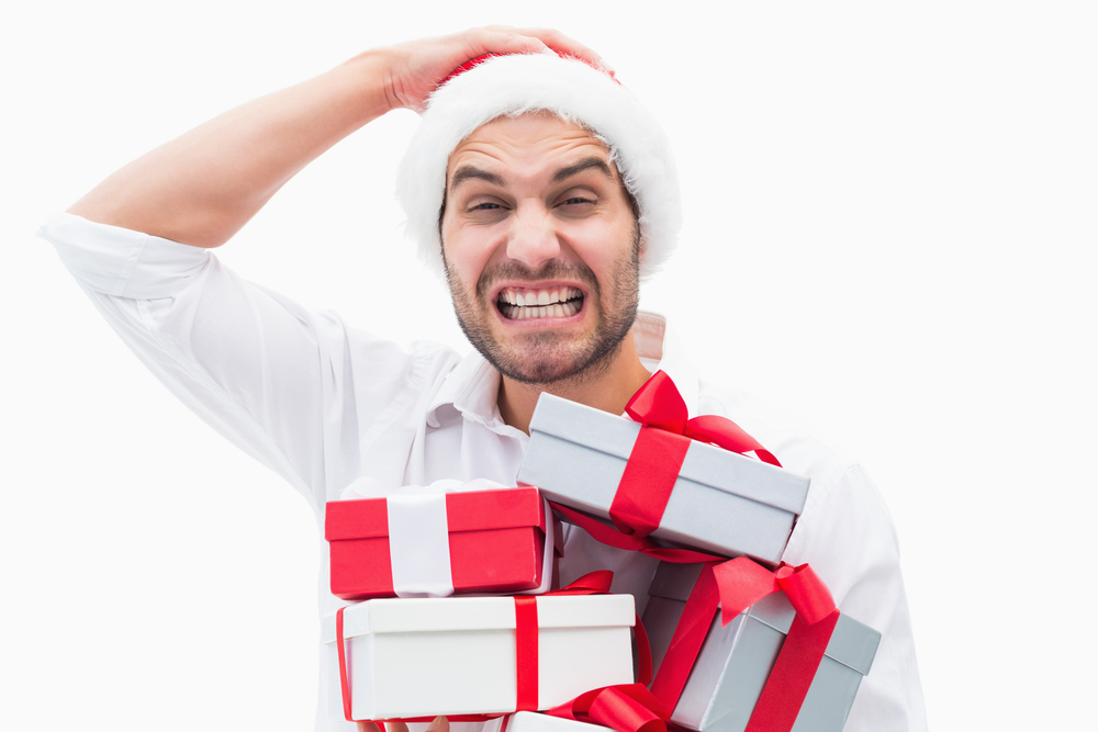 Stressed festive man holding gifts on white background